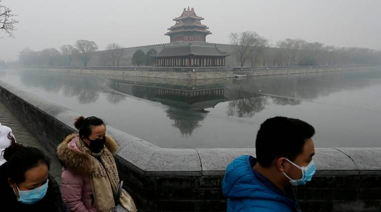 People wearing masks walk past the Turret of the Forbidden City on a heavily polluted day in Beijing Tuesday, Dec. 8, 2015. (AP Photo/Andy Wong)