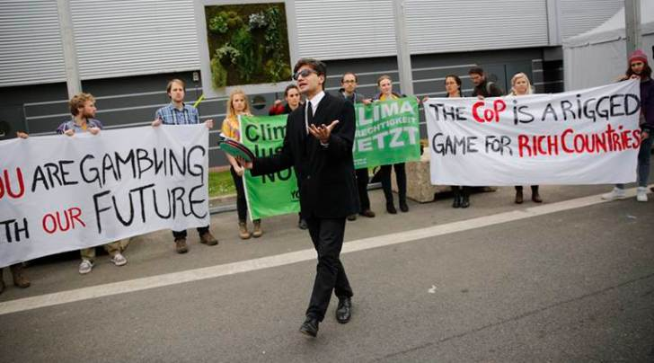 Activists hold banners at the COP21, the United Nations Climate Change Conference Tuesday, Dec. 1, 2015 in Le Bourget, north of Paris. A dozen activists unfurled banners and performed a skit outside the exhibition halls hosting high-stakes climate talks through Dec. 11. (AP Photo/Christophe Ena)