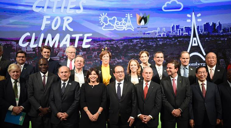French President Francois Hollande, center, poses with Paris Mayor Anne Hidalgo, center left, London Mayor Boris Johnson, left, former New York Mayor Michael Bloomberg, 3rd right, Seoul Mayor Park Won-soon, right, Istanbul Mayor Kadir Topbas, 3rd left,  Dakar Mayor Khalifa Sall, 2nd left, and Rio de Janeiro Mayor Eduardo Paes, 2nd right, pose for a group photo during a summit on climate with local representatives at Paris townhall, France, as part of the World Climate Change Conference (COP21), Friday, Dec. 4, 2015. (Stephane de Sakutin/Pool Photo via AP)
