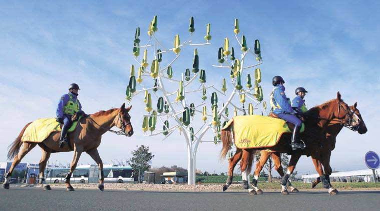 At the venue of COP21 outside Paris, French mounted police patrol beside a 'Wind Tree', each of whose leaves functions like a mini wind turbine. (Source: AP)
