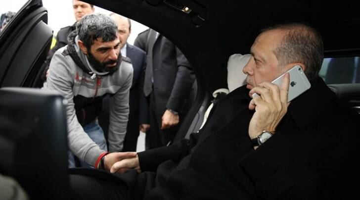 """Turkish President Recep Tayyip Erdogan, right, takes Vezir Cakras by hand while speaking on his mobile phone inside his car stationed over the Bosporus Bridge in Istanbul, Friday, Dec. 25, 2015. Erdogan's office says the Turkish president has talked Cakras out of jumping off a bridge to commit suicide. Television footage on Friday showed Erdogan's motorcade stopping over Istanbul's Bosporus Bridge where a man was apparently contemplating jumping off. An official from Erdogan's office told the Associated Press that Vezir Cakras was depressed because of """"family issues."""" (Yasin Bulbul, Presidential Press Service Pool via AP Photo )"""