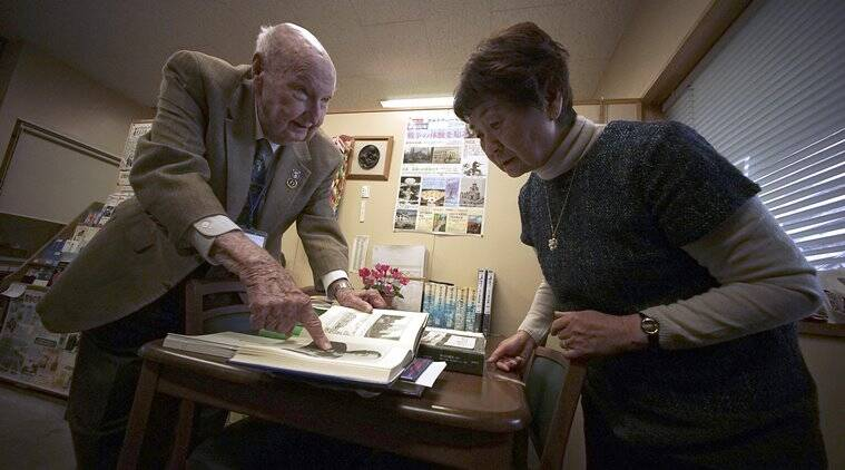 "Fiske Hanley, right, of Fort Worth, TX, an American World War II veteran who took part in firebombing of Tokyo and was later held captive by the Japanese 70 years ago, shows some pages of his book ""Accused American War Criminal"" to survivor Haruyo Nihei, left, a museum storytelling volunteer, talk at the Center of the Tokyo Raids and War Damage in Tokyo Wednesday, Dec. 9, 2015. Hanley, 95, was on a B-29 as engineering crew in the March 10, 1945 firebombing that nearly destroyed eastern Tokyo, with overnight death toll exceeding 100,000. Hanley is also a victim of brutality by Japan's ""kempeitai"" military police during his captivity after his B-29 crashed.(AP Photo/Eugene Hoshiko)"