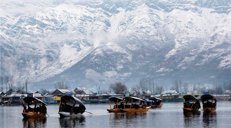 Srinagar: Tourists enjoy Shikara rides at Dal Lake in Srinagar on Friday as snow covered Zabarwan mountains are seen in the background after the season's first snowfall. PTI Photo  (PTI12_11_2015_000124B)