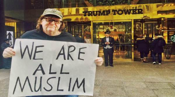 American director Michael Moore holds a placard saying 'We are all Muslims' in front of Trump Tower/ Facebook