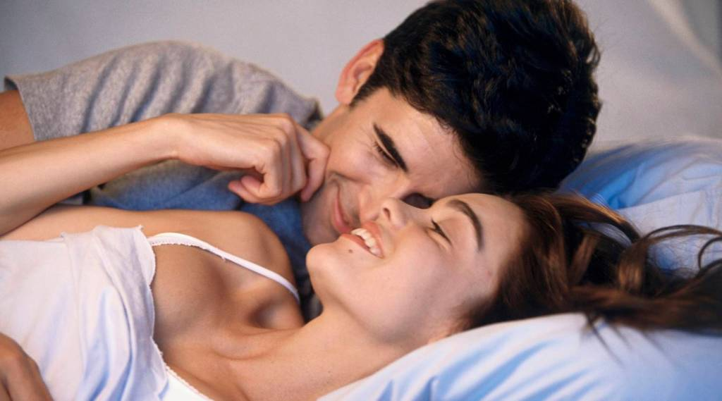 Young couple lying on a bed laughing