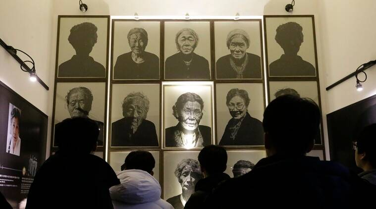 "South Korea high school students look at portraits of late former ""sex salves"" who were forced to serve for the Japanese Army during World War II at the House of Sharing, the home for the living sex slaves, in Gwangju, South Korea, Tuesday, Dec. 29, 2015. A day after trumpeting an ""irreversible"" settlement of a decades-long standoff over Korean women forced into sexual slavery by Japan's WWII military, there's relief among South Korean and Japanese diplomats, fury among activists and many of the elderly victims and general public indifference in both countries. (AP Photo)"