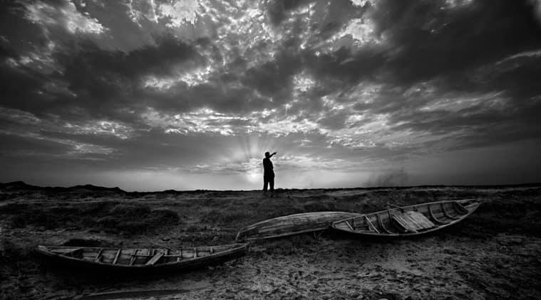 A man points to his home across the river Naf in Noapara, Bangladesh. (Source: Saiful Huq Omi)