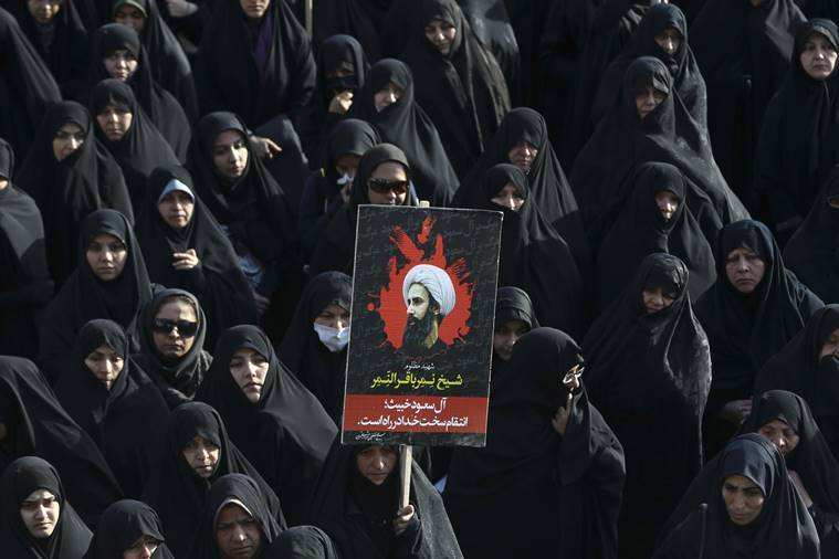 An Iranian woman holds up a poster showing Sheikh Nimr al-Nimr, a prominent opposition Saudi Shiite cleric who was executed last week by Saudi Arabia, in Tehran, Iran. (AP Photo/File)