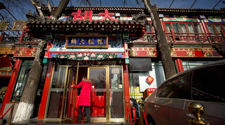 A hostess walks through the door of a branch of the Hu Da hot pot restaurant chain in Beijing, Friday, Jan. 22, 2016. Thirty-five restaurants across China, including the popular Beijing hot pot chain, have been prosecuted or are under investigation for illegally using opium poppies as seasoning, one of the more unusual practices bedeviling the country's food regulators. (AP Photo/Mark Schiefelbein)