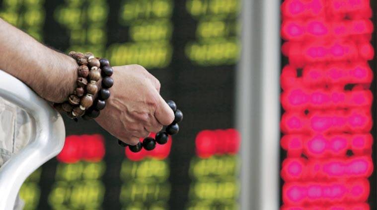 An investor holds onto prayer beads as he watches a board showing stock prices at a brokerage office in Beijing. (source: Reuters)