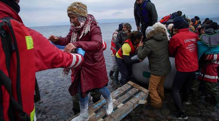 Members of the Greek Red Cross and other volunteers help migrants and refugees to disembark from an inflatable boat after crossing the Aegean sea from Turkey to the Greek island of Lesbos, on Tuesday, Jan. 26, 2016. More than 850,000 people, most fleeing conflict in Syria and Afghanistan, entered Greece by sea in 2015, according to the UNHCR, and already in 2016, some 35,455 people have arrived despite plunging winter temperatures. (AP Photo/Mstyslav Chernov)