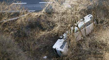 A bus lies after it veered off to the opposite lane on a mountain road in Karuizawa, Nagano prefecture, central Japan Friday, Jan. 15, 2016. Rescue officials say the overnight tour bus on its way to a ski resort in central Japan slid down the mountainside, killing at least more than a dozen passengers. (Kyodo News via AP) JAPAN OUT, NO SALES