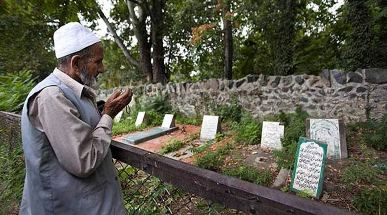 A Kashmiri man prays near an unmarked grave inside a martyrs graveyard in Srinagar, Kashmir. (Source: AP file photo)