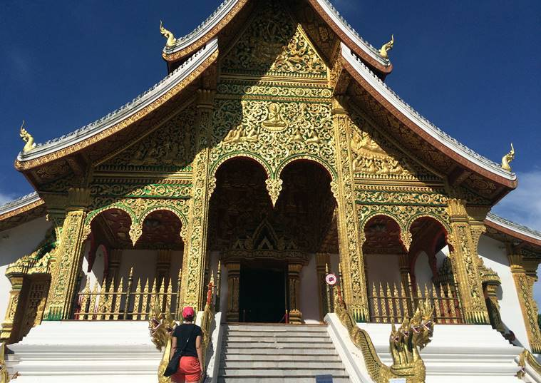 In this Sept. 8, 2014 photo, a tourist visits the Haw Pha Bang temple in the grounds of the Palace Museum in Luang Prabang, Laos. It is officially described as the best-preserved city in Southeast Asia, a bygone seat of kings tucked into a remote river valley of Laos. Luang Prabang weaves a never-never land spell on many a visitor with its tapestry of French colonial villas and Buddhist temples draped in a languid atmosphere. (AP Photo/Mark Baker)