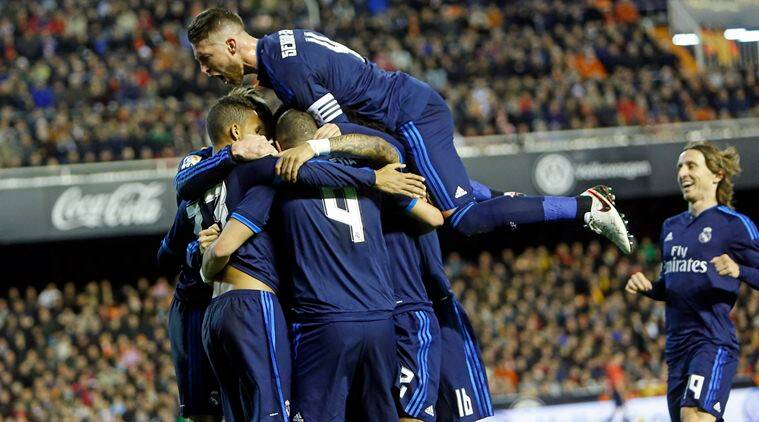 Real Madrid's Karim Benzema, back to the camera no. 4, celebrates with teammates after scoring against Valencia during a Spanish La Liga soccer match at the Mestalla stadium in Valencia, Spain, Sunday, Jan. 3, 2016. (AP Photo/Alberto Saiz)