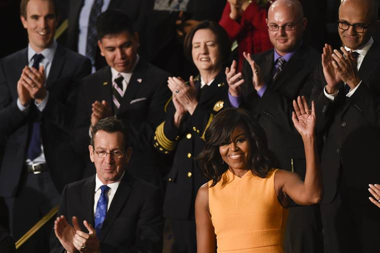 First lady Michelle Obama, standing next to Connecticut Gov. Dannel Malloy, waves on Capitol Hill in Washington, Tuesday, Jan. 12, 2016, prior to the start of President Barack Obama's State of the Union address before a joint session of Congress. (AP Photo/Susan Walsh)