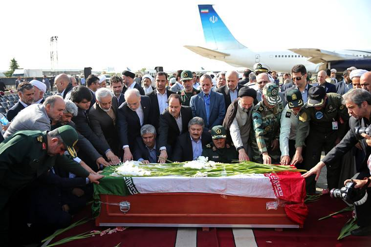 In this Oct. 3, 2015 file photo, Iranian officials pray as they touch the coffin of a dead hajj pilgrim who was killed in a deadly stampede in Mina near Mecca in Saudi Arabia, at Mehrabad airport in Tehran, Iran.