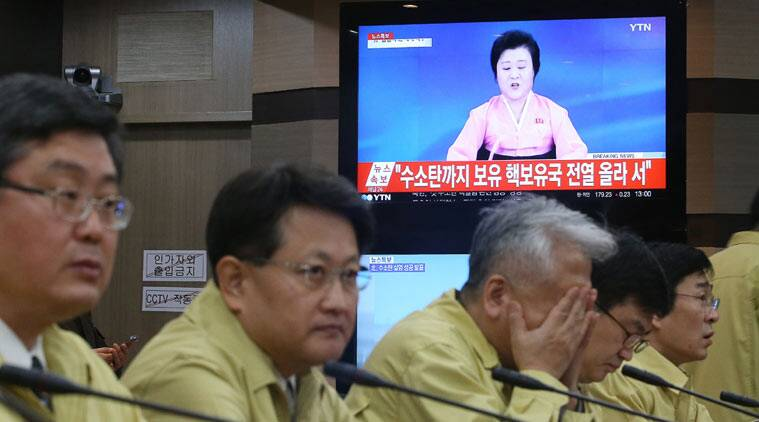 South Korean Foreign Ministry officials attend an emergency meeting as a TV news program showing North Korea's announcement at the ministry in Seoul, South Korea, Wednesday, Jan. 6, 2016. (AP Photo)