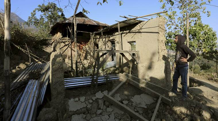 REFILE - ADDING RESTRICTION  A man stands next to a damaged house after an earthquake at P.Molding village on the outskirts of Imphal, India, January 4, 2016. A powerful earthquake struck northeast India and Bangladesh on Monday, killing at least 11 people and injuring nearly 200, with efforts to reach remote areas where people may be trapped hampered by severed power lines and telecommunication links. REUTERS/Stringer  FOR EDITORIAL USE ONLY. NO RESALES. NO ARCHIVE.