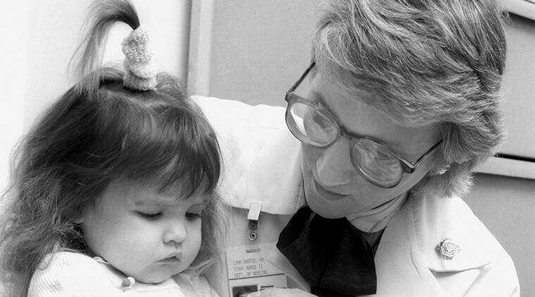 In this June 1988 photo provided by Children's Hospital of Wisconsin, Lynn Bartos, pediatric nurse for Children's Hospital of Wisconsin Gastroenterology Clinic, holds Nicole Frye. The nurse and family were featured on the cover of the hospital's nursing magazine in 1988 for a story about long term care. (Source: AP)