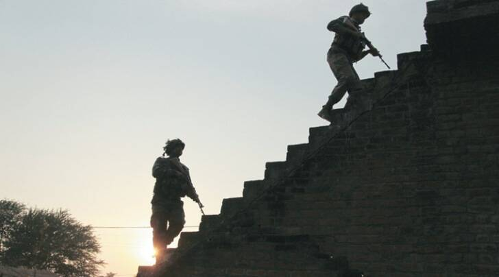 Soldiers climb up the stairs of a residential building outside the Indian air force base in Pathankot on Sunday evening as the gunbattle continued. (AP Photo)