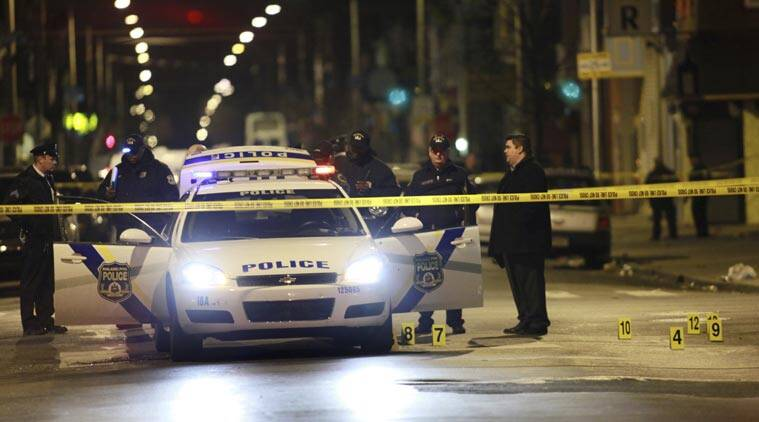 Officials investigate the scene of a shooting Friday, Jan. 8, 2016, in Philadelphia. A Philadelphia police officer was shot multiple times by a man who ambushed him as he sat in his marked police cruiser, authorities said. (AP Photo)