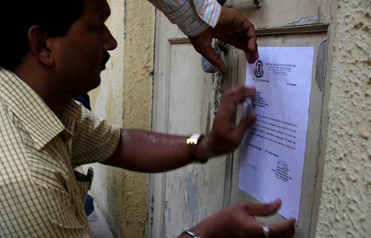 A CBI official pastes a summon notice on the door of Amit Shah's residence. Express Photo/File