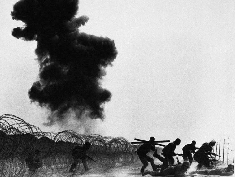 In this March 10, 1984 file photo, Iranian troops advance despite obstacles set by Iraqi forces in the Manjnoon Islands, Iraq. Smoke in background rises from Iraqi armored units set afire by Iranian forces. (AP Photo/File)