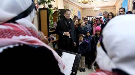 CORRECTS FROM IN AMMAN TO 20 KILOMETERS OUTSIDE OF AMMAN. German Minister for Economic Cooperation and Development Gerd Mueller speaks with Syrian refugee children during his visit to Baqaa Refugee Camp, 20 kilometers outside of Amman, Jordan, Tuesday, Jan. 26, 2016. (AP Photo/Raad Adayleh)