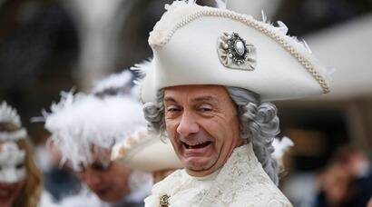 A man impersonating Giacomo Casanova smiles in St. Marks' Square, during the Carnival, in Venice, Italy, Sunday, Jan. 24, 2016. . Authorities have increased surveillance throughout the city and increased the number of officers on patrol, both under-cover and in uniform, but backed down on a proposal to ban revelers from wearing masks on the occasion of the Venice Carnival. (AP Photo/Luca Bruno)