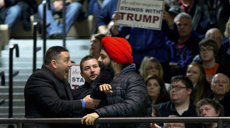A protester, right, is removed after interrupting Republican presidential candidate Donald Trump as he speaks at a rally at Muscatine High School in Muscatine, Iowa. AP Photo