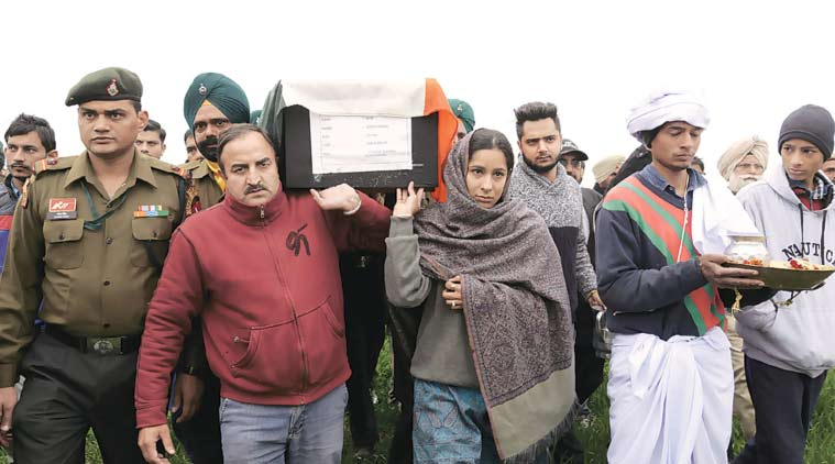 Madhu Radha carries her father Fateh Singh's coffin at Jhandha Gujjaran, in Gurdaspur, on Monday. (Express photo by: Rana Simranjit Singh)