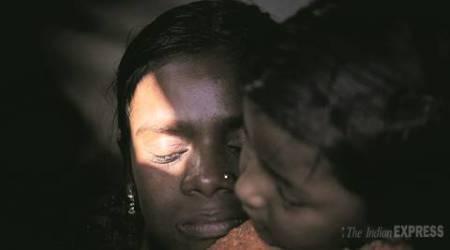 Bahaduri with a child from the neighbourhood after she lost her children. Express Photo/Oinam Anand