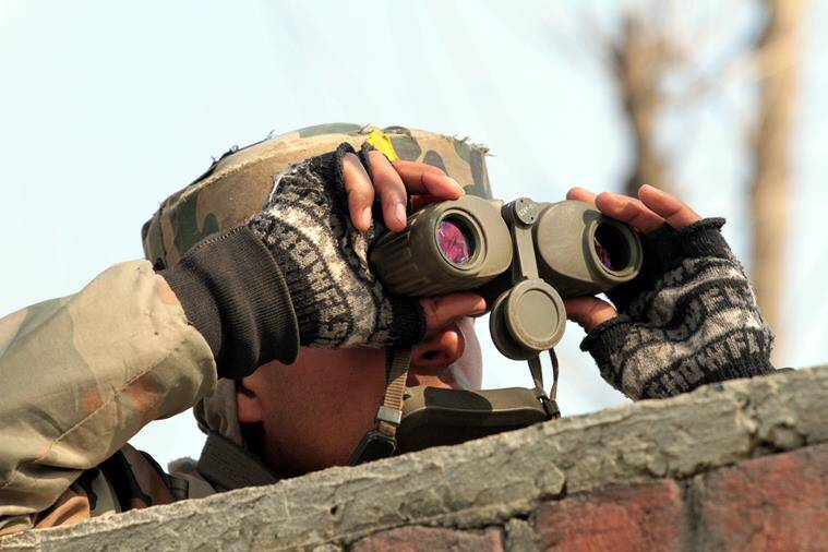 Army soldier uses binocular to locate militant positions near the site of a gunbattle in Sempora Pampore, some 15 km south of Srinagar on Monday. The encounter that started on saturday (FEB 20) entered third day on Monday.EXPRESS PHOTO BY SHUAIB MASOODI 22-02-2016.