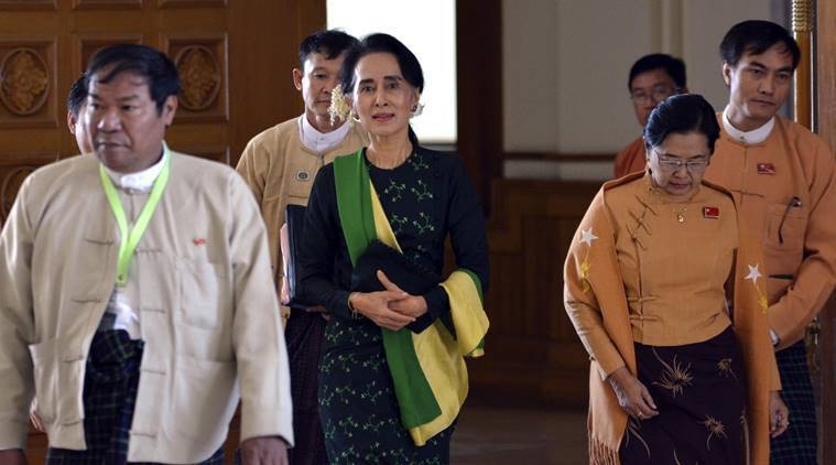 Pro-democracy leader Aung San Suu Kyi, center, walks along with lawmakers of her National League for Democracy (NLD) party to attend the inauguration session of Union Parliament. AP Photo