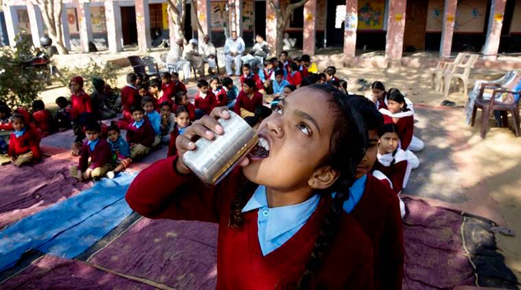 A girl takes a pill at a government school in Rajasthan as part of a national deworming drive, on Wednesday. (Source: AP)