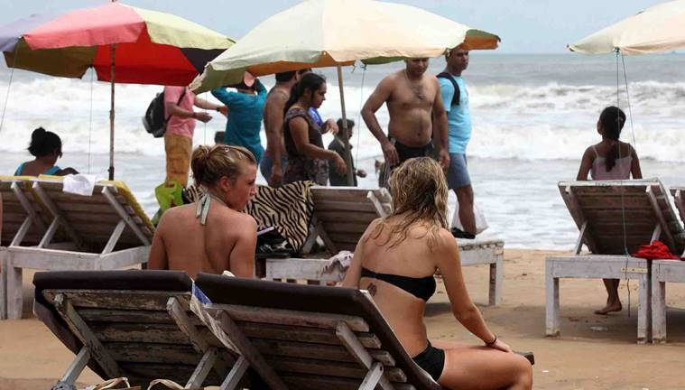 Tourists, both international and domestic, relax at a beach in Goa. Express Photo