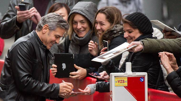 U.S. actor George Clooney signs autographs as he arrives for a photo call for the film 'Hail Caesar' in Berlin, Germany Thursday Feb. 11, 2016. The Berlin Film Festival 'Berlinale' runs until Feb. 21, 2016. (Bernd von Jutrczenka/ dpa via AP)