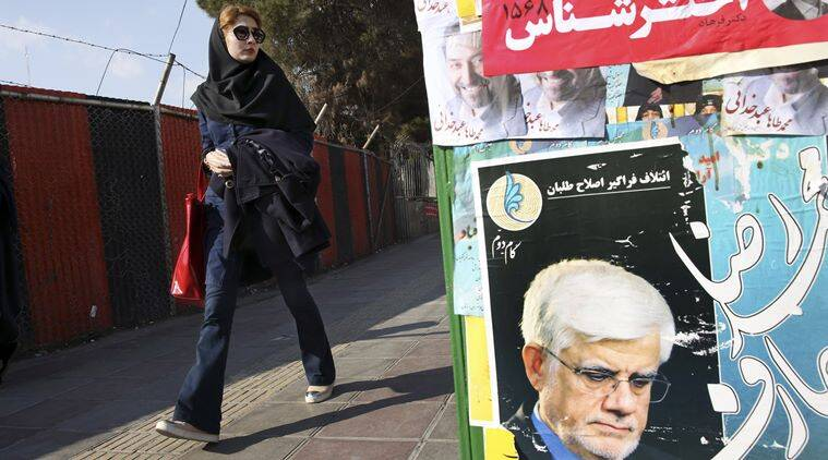 An Iranian woman walks past electoral posters of candidates of parliamentary elections in a sidewalk in Vanak square in northern Tehran, Iran, Thursday, Feb. 25, 2016. (Source: AP)