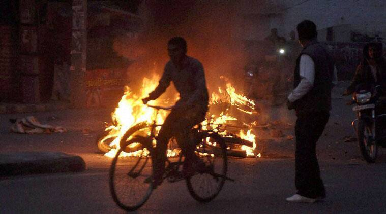 Jat community members torch a motorcyle during their agitation for reservation in Rohtak on Thursday. (PTI Photo)