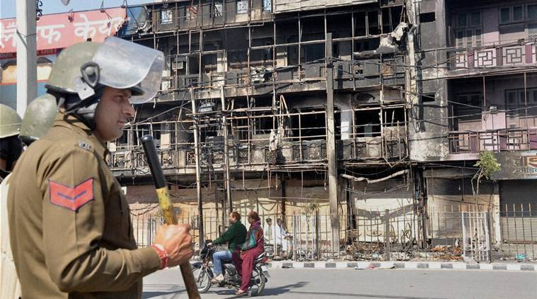 Police personnel stand guard in Rohtak where thousands of shops and private properties of the non-Jats were targetted by Jat protesters during their agitation for reservation, in Rohtak on Monday. (Source: PTI)