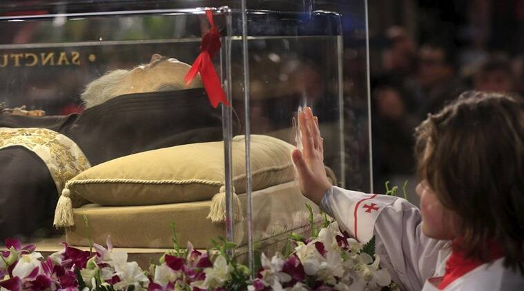 An altar boy touches the glass where the exhumed body of the mystic saint Padre Pio lies in the Catholic church of San Lorenzo fuori le Mura in Rome. (Photo: Reuters)