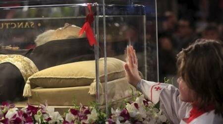 An altar boy touches the glass where the exhumed body of the mystic saint Padre Pio lies in the Catholic church of San Lorenzo fuori le Mura in Rome, February 3, 2016. The body of one of the most popular Roman Catholic saints, the mystic monk Padre Pio began an overland journey in a crystal coffin on Wednesday to go on display at the Vatican .    REUTERS/Yara Nardi