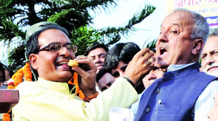 MP Chief Minister S S Chouhan celebrates with Maihar winner Narayan Tripathi. Express