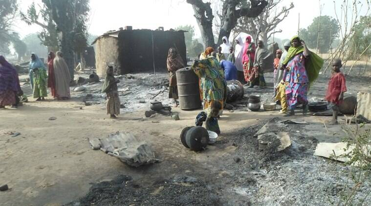 Women and children look at burnt out houses following an attack by Boko Haram in Dalori village 5 kilometers (3 miles) from Maiduguri, Nigeria, Sunday Jan. 31, 2016. A survivor hidden in a tree says he watched Boko Haram extremists firebomb huts and listened to the screams of children among people burned to death in the latest attack by Nigeria' s homegrown Islamic extremists. (AP Photo/Jossy Ola)