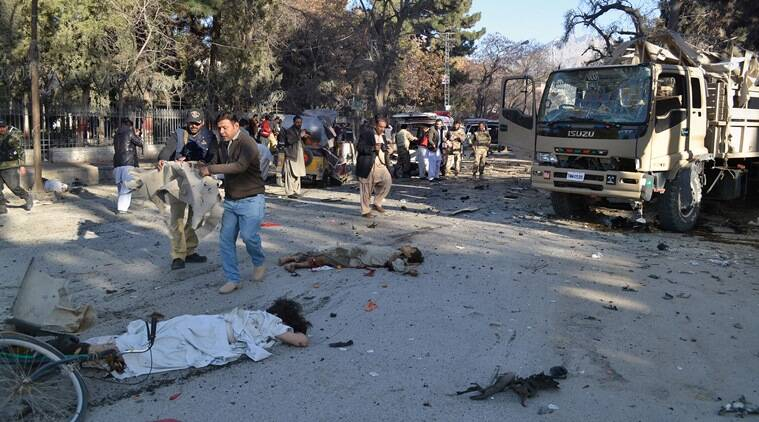 NOTE: GRAPHIC CONTENT -- A police officer and volunteer rush to cover a body at the site of a deadly suicide bombing in Quetta, Pakistan, Saturday, Feb. 6, 2016. A suicide bomber riding on a bicycle targeted a vehicle carrying security forces in southwestern Pakistan on Saturday, killing some people and wounding many. (AP Photo/Arshad Butt)