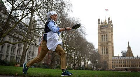 Norwich South MP Clive Lewis takes part the annual Rehab Parliamentary Pancake Race, in which MPs, Lords and members of the media race each other on pancake day to raise money for the charity Rehab, in Victoria Tower Gardens, London, Tuesday, Feb. 8, 2016. (Stefan Rosseau/PA via AP)       UNITED KINGDOM OUT      -    NO SALES      -     NO ARCHIVES