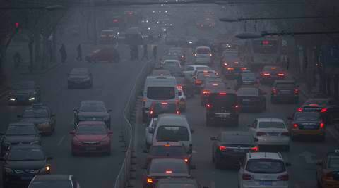FILE - In this Dec. 25, 2015, file photo, pedestrians make their way across a busy intersection on a day with severe air pollution in Beijing. Average concentrations of air particulates in 189 Chinese cities fell by 10 percent in 2015, according to a new Greenpeace report, a sign that pollution overall is decreasing even as catastrophic levels of smog this winter in northern China effectively shut down schools and roads. (AP Photo/Mark Schiefelbein, File)
