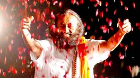 Spiritual leader Sri Sri Ravi Shankar showering flower petals on devotees during his Satsang at Leisure Valley in Sector 10 of Chandigarh on Tuesday, October 22 2013. Express photo by Sumit Malhotra