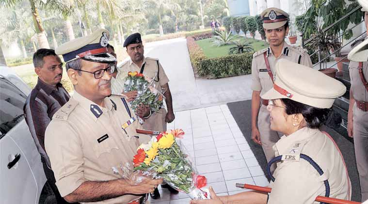 A police officer greets the  newly appointed Police Commissioner of Surat City Ashish Bhatia in Surat on Wednesday. (Source: PTI)